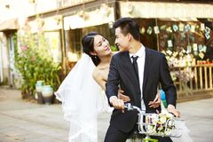 Romantic asian newly-wed riding a bicycle Royalty Free Stock Photo