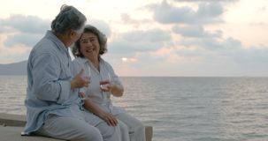Romantic asian senior couple watching sunset and enjoying a glass of wine on beautiful tropical beach.