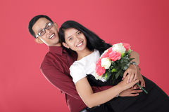 Romantic Asian teen couple smile and pose with intimate hug. Romantic young Asian couple smile and pose with intimate hug, over red background Stock Photo