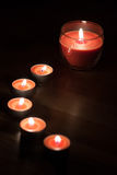 Romantic atmosphere. Orange colored tea candles on the floor Stock Photography