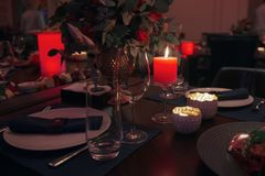 Romantic atmosphere in a luxury restaurant. Glowing candles in low light. Beautiful decoration royalty free stock images