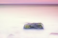 Romantic atmosphere in peaceful morning at sea. Big boulders sticking out from smooth wavy sea. Pink horizon Stock Photo
