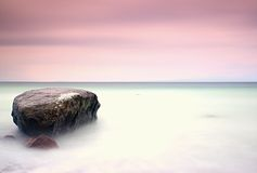 Romantic atmosphere in peaceful morning at sea. Big boulders sticking out from smooth wavy sea. Pink horizon Stock Images