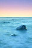 Romantic atmosphere in peaceful morning at sea. Big boulders sticking out from smooth wavy sea. Pink horizon Stock Photography
