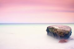 Romantic atmosphere in peaceful morning at sea. Big boulders sticking out from smooth wavy sea. Pink horizon. With first hot sun rays.Vintage Style Toned effect Stock Photography