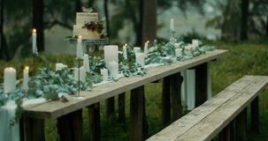 Romantic atmosphere. Table served for two. Leaves, flowers, two-tiered cake with berries and candles are covering the stock video footage