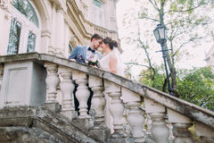 Romantic attractive newlywed couple in love posing on ancient stairs at the old austrian palace Stock Photo