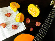 Romantic autumn composition. Made of pumpkin, song book, dried rose petals and guitar stock images
