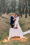 Romantic autumn pine forest picknick with candles. Happy newlywed couple celebrating their marriage Royalty Free Stock Photo
