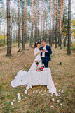 Romantic autumn pine forest picknick of happy newlywed couple Stock Photos