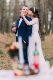 Romantic autumn pine forest picknick. Happy newlywed couple celebrating their marriage Royalty Free Stock Images