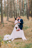 Romantic autumn pine forest picknick of happy newlywed pair Royalty Free Stock Images