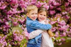 Romantic babies. Couple kids walk sakura tree garden. Tender love feelings. Little girl and boy. Romantic date. Spring. Time to fall in love. Kids in love pink royalty free stock photos