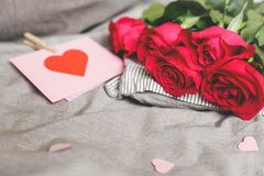 Romantic background with copy space. Beautiful roses and Valentine card with heart. Selective focus royalty free stock images