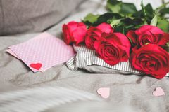 Romantic background with copy space. Beautiful roses and Valentine card with heart. Selective focus royalty free stock photos