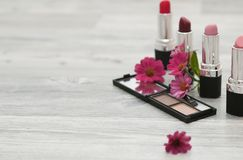 The romantic background for cosmetics with flowers and cosmetics. Set of beautiful red lips on white stock photos