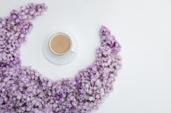 Romantic background with a cup of coffee, lilac flowers on a white table. Top view, place for text.  stock photography