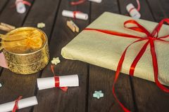 Romantic background. Gift box with rolled wishes paper gift pack on wooden board. Romantic background. Gift box with rolled wishes paper gift pack on the wooden royalty free stock photos