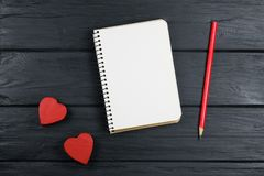 The romantic background with notepad, pencil and two red hearts. The romantic background with notepad, pencil and red hearts royalty free stock photography