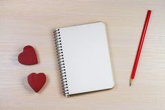 The romantic background with notepad, pencil and two red hearts. The romantic background with notepad, pencil and two red hearts on the wooden table royalty free stock photo