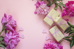 Romantic background with peonies, gift boxes and hearts on pink. Royalty Free Stock Photo