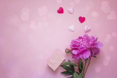 Romantic background with peony, gift box and hearts on pink. Stock Photo