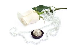 Romantic background with rose, sweets and pearl. On white Stock Photos
