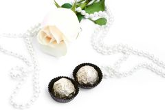 Romantic background with rose, sweets and pearl. On white Stock Images