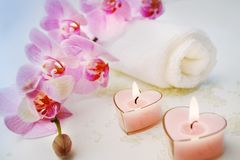 Romantic bath. Tender orchids, candles, towels and salt on the table Royalty Free Stock Photography