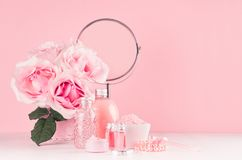 Romantic bathroom interior in pastel pink and silver color - flowers, round mirror, bath accessories, cosmetic products - cream. Romantic bathroom interior in stock image