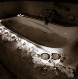 Romantic bathtub with candles, flowers and couple of wineglasses Stock Photos