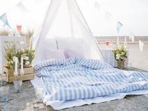 Romantic beach camping. Bohemian style outdoor picnic. Bright scene of romantic beach dining Stock Image