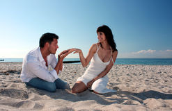 Romantic beach couple smiling. A romantic couple pair of man and woman 20s smiling and being in love at the beach in summertime royalty free stock image