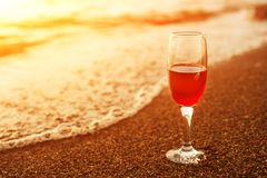 Romantic beach scene: glass of red wine at sunset near water line.  royalty free stock images