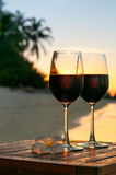 Romantic beach scene: two glasses of red wine at sunset near water Stock Images