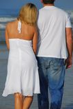 Romantic beach stroll. Young couple having romantic stroll on the beach stock photography