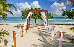 Romantic Beach Wedding Location in Jamaica. A view of the Caribbean Sea in the distance through a lovely beach side pergola decorated as a wedding venue at the Royalty Free Stock Photo
