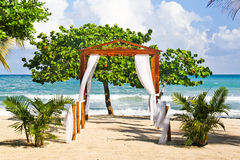 Romantic Beach Wedding Spot in Jamaica. A view of the Caribbean Sea in the distance through a lovely beach side pergola decorated as a wedding venue at the Stock Image