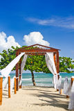 Romantic Beach Wedding Spot. A view of the Caribbean Sea in the distance through a lovely beach side pergola decorated as a wedding venue at the Couples Negril stock photo