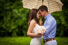 Romantic beautiful couple hugging under elegant umbrella outdoor Royalty Free Stock Images