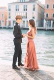 Romantic beautiful couple in Venice happy together standing on the background of venetian canal and buildings. Italy, Europe. Romantic beautiful couple in stock photography