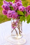 Romantic, beautiful lilac flowers in the glass vase. Outside, on the garden table Royalty Free Stock Photography