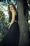 Romantic, beautiful woman in a forest, redhead with long hair. Beauty royalty free stock images