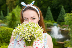 Romantic beautiful young woman smelling flowers outside Stock Photos