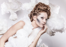 Romantic beauty with magnificent hair wandering in clouds. Studio fashion portrait. Stock Photography