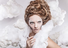 Romantic beauty with magnificent hair wandering in clouds. Studio fashion portrait. Stock Photos