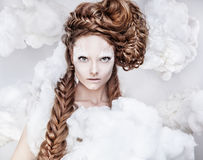 Romantic beauty with magnificent hair wandering in clouds. Studio fashion portrait. Royalty Free Stock Image