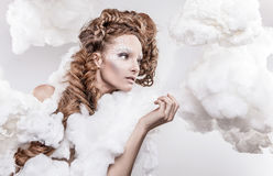 Romantic beauty with magnificent hair wandering in clouds. Studio fashion portrait. Stock Images