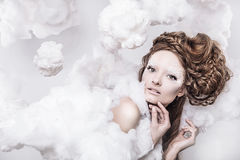 Romantic beauty with magnificent hair wandering in clouds. Studio fashion portrait. Royalty Free Stock Photo