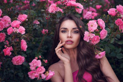 Romantic beauty portrait of woman in pink roses. Fashion style beauty romantic portrait of young pretty beautiful woman with long curly hair posing between pink Royalty Free Stock Photography